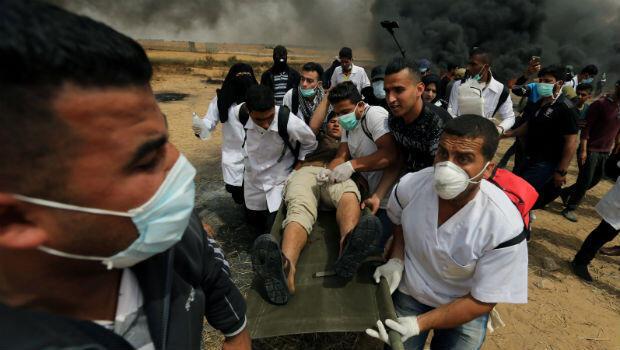 Palestino herido es evacuado durante los enfrentamientos con las tropas israelíes.