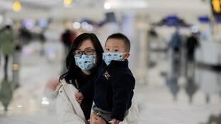 أم وطفلها يرتديان كمامات خوفا من العدوى بالفيروس الجديد بمطار بكين-داكسينغ، 21 كانون الثاني/يناير 2019.