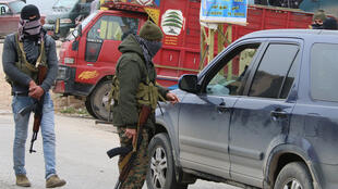 Des hommes armés arrêtent des voitures dans le village libanais de Bazzalié, d'où est originaire le policier tué.