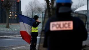 Un 'chaleco amarillo' con una bandera francesa durante el desmantelamiento de una zona de ocupación cerca de la autopista A2 París-Bruselas, en Fontaine-Notre-Dame. Francia, 14 de diciembre de 2018.