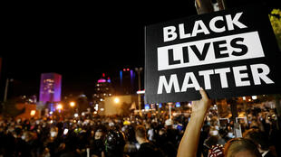 """A demonstrator holds up a """"Black Lives Matter"""" sign during a protest over the death of a Black man, Daniel Prude, after police put a spit hood over his head during an arrest on March 23, in Rochester, New York, U.S. September 6, 2020."""