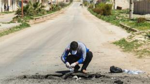 Un homme syrien récolte des échantillons sur le site d'une présumée attaque chimique à Khan Cheikhoun, dans la province d'Idlib, le 5 avril 2017.