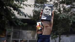 Fans of Iranian musician Mohammad-Reza Shajarian hold up his image on a phone as they mourn his death