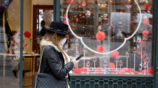 A woman walks down Paris's Champs-Elysèes boulevard as shops reopened for the first time in eight weeks as France lifted its nationwide Covid-19 lockdown on May 11.