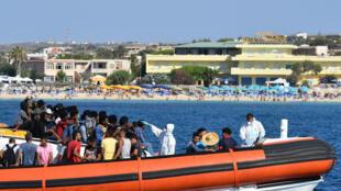 مهاجرون يخضعون للفحص الطبي على متن قاربهم لدى وصولهم إلى جزيرة لامبيدوسا الإيطالية في الأول من آب/أغسطس 2020