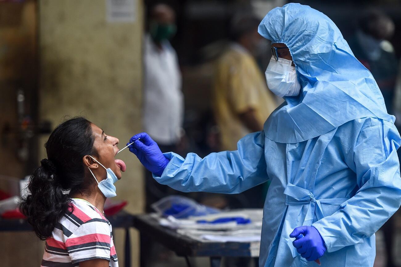 A health worker takes a swab sample from a resident getting tested for the COVID-19 coronavirus near residential buildings in Mumbai on July 16, 2020.