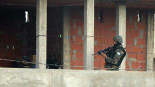 Un membre des forces de l'ordre tunisiennes donnant l'assaut contre la maison où des terroristes présumés étaient retranchés.