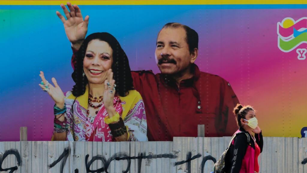 Esta mujer camina frente a un mural donde aparecen el presidente Daniel Ortega y la vicepresidenta Rosario Murillo en Managua, Nicaragua, el 27 de marzo de 2020.