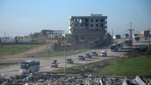 Les forces d'opposition syriennes escortent un convoi d'évacuation de civils et de rebelles, le 19 mars 2017.