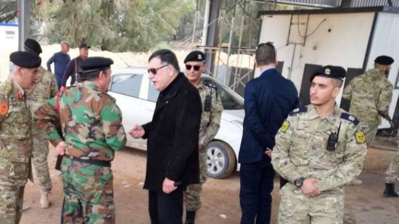 Fayez al-Sarraj (en noir), le chef du gouvernement d'union nationale (GNA) en Libye, discute avec les militaires près d'un barrage militaire repris aux forces rivales du maréchal Haftar.