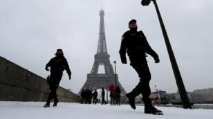 La policía francesa patrulla cerca de la Torre Eiffel en París bajo la nieve que cae a medida que el clima invernal continúa en el norte de Francia, el 9 de febrero de 2018.