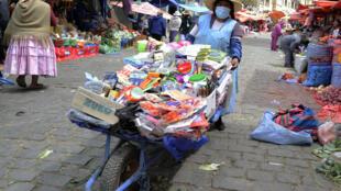 Una mujer indígena aymara lleva una máscara facial mientras ofrece productos de limpieza para la venta en el mercado Rodríguez en La Paz, el 1º de septiembre de 2020