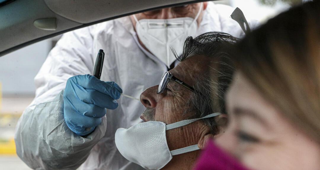 El trabajador de la salud Patricio Candia toma una muestra de hisopo nasal de un hombre en un nuevo sitio de prueba de coronavirus, afuera de un supermercado en Santiago, Chile, el sábado 27 de junio de 2020.