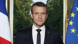 Le président de la République pose dans son bureau avec les jardins de l'Élysée en arrière-plan.