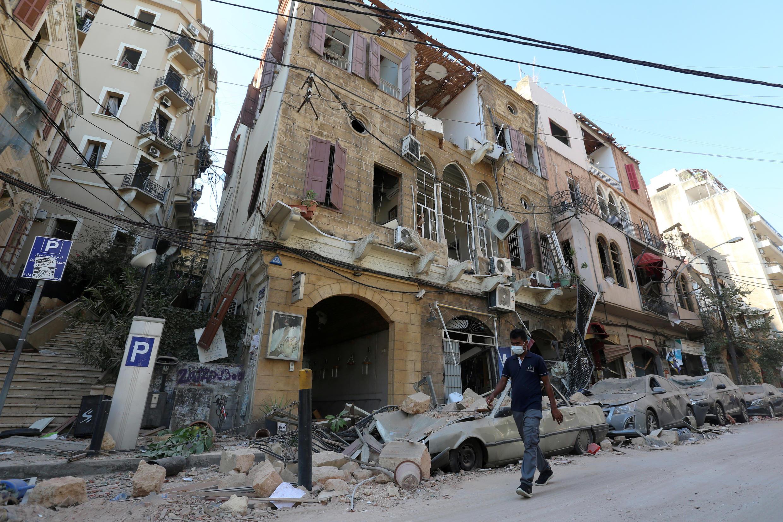 Un hombre con una mascarilla pasa junto a edificios y vehículos dañados cerca del lugar de la explosión del martes en el área del puerto de Beirut, Líbano, el 5 de agosto de 2020.