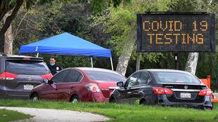 A police officer mans the entrance to a coronavirus (COVID-19) testing center in Hansen Dam Park in Pacoima, California