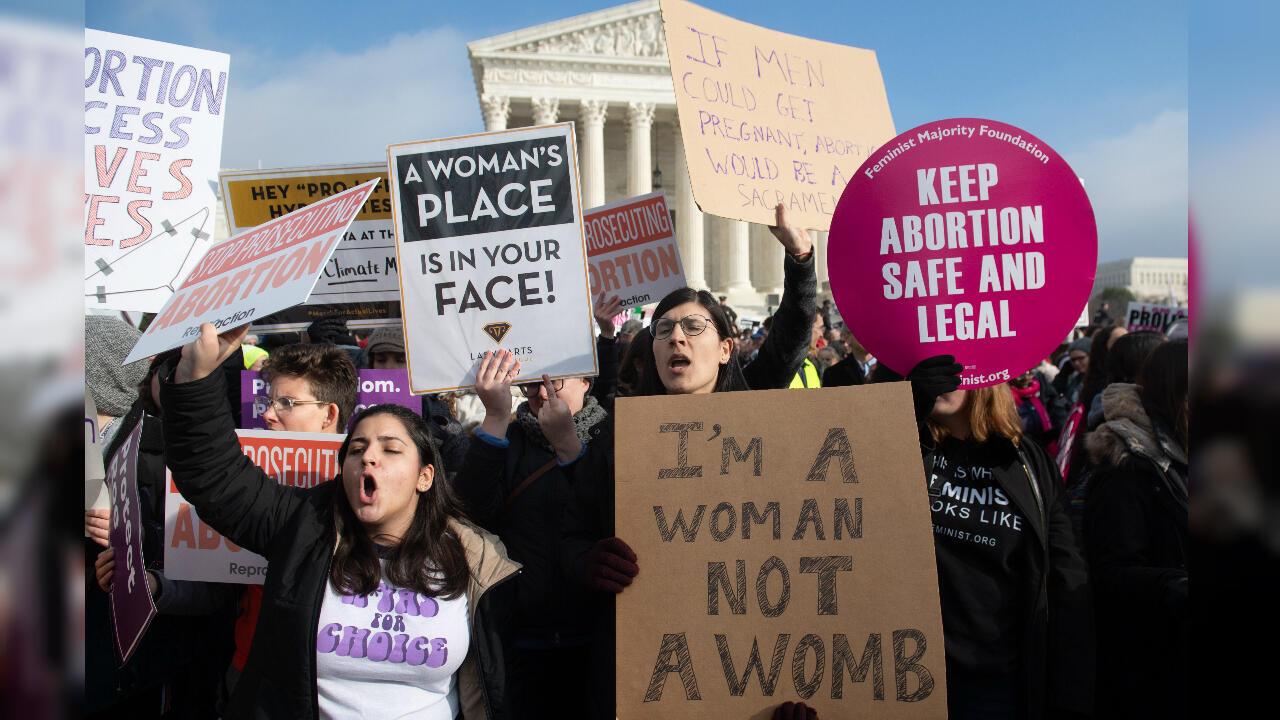 """Manifestantes a favor del aborto sostienen pancartas en respuesta a los activistas contra el aborto que participan en la Marcha por la Vida, un evento anual para conmemorar la legalización del aborto en EE. UU. Una de las pancartas dice """"Soy una mujer, no una matriz"""". Washington, EE. UU., el 18 de enero de 2019."""