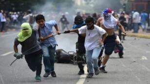 متظاهرون يجرون دراجة نارية محترقة للشرطة خلال تظاهرات ضد انتخاب جمعية تاسيسية 30 تموز/يوليو 2017