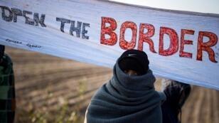 """Des migrants attendent à la frontière serbo-croate avec une banderole """"Ouvrez les frontières"""", le 14 novembre 2016."""