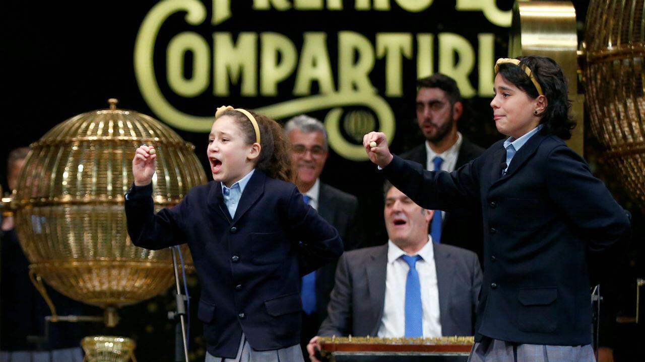 """Dos niñas sostienen el número ganador de """"El Gordo"""", el mayor premio de la Lotería de Navidad de España, en Madrid, el 22 de diciembre de 2018."""