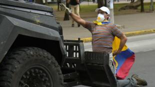 Un manifestant se tient devant un véhicule blindé de la police, à Quito, le 4 octobre 2019.