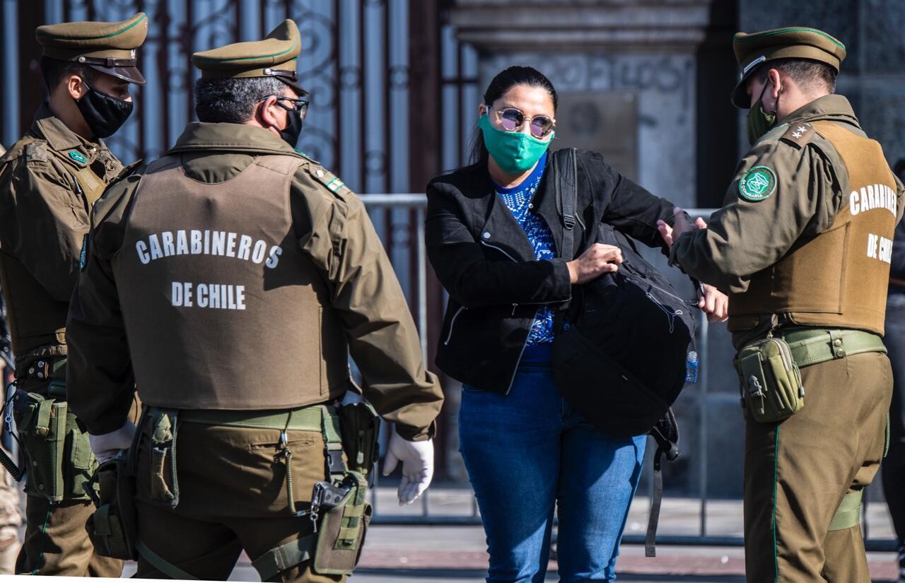 Una ciudadana inspeccionada por agentes en un punto de control durante la cuarentena total obligatoria debido a la pandemia, en Santiago, Chile, el 10 de junio de 2020.
