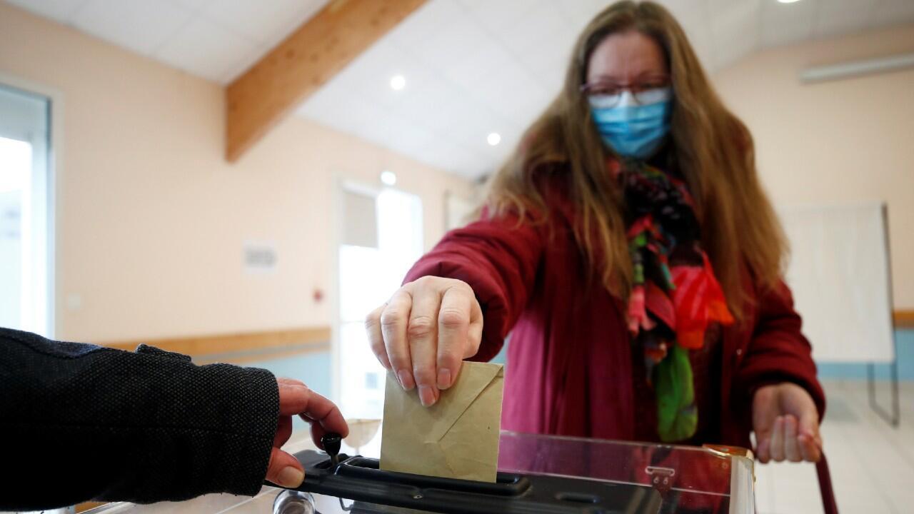 Una mujer con una mascarilla emite su voto durante la primera vuelta de las elecciones a la alcaldía, mientras Francia se enfrenta a un brote de la enfermedad por coronavirus (COVID-19), en Cracovia, en el departamento de Morbihan, Francia, el 15 de marzo de 2020.