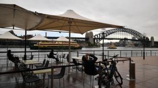 Clientes en la terraza de una cafetería en el puerto de Sídney, después de siete semanas de restricciones a causa de la epidemia de coronavirus, el 15 de mayo de 2020