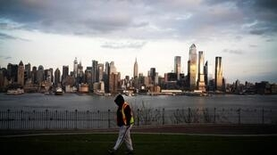 The Empire State Building and the skyline of New York are seen while a man walks around a local park in Weehawken, New Jersey, as the coronavirus disease (COVID-19) outbreak continues in New York, U.S., March 22, 2020.