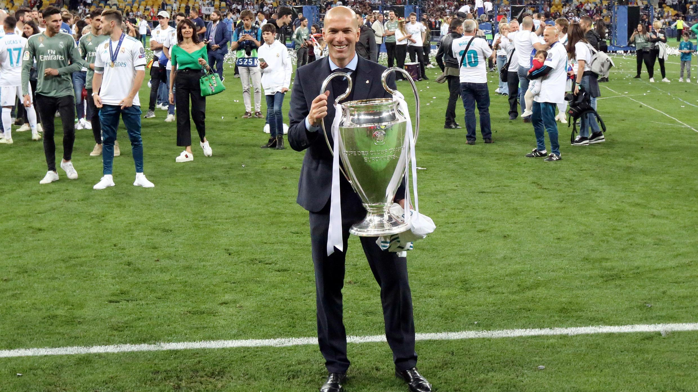 El entrenador del Real Madrid posa con el trofeo mientras celebra después de ganar la Liga de Campeones.