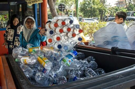 Dozens of people clutching bags full of plastic bottles and disposable cups queue at a busy bus terminal in the Indonesian city of Surabaya -- where passengers can swap trash for travel tickets