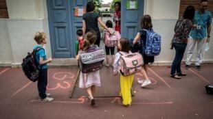 Parents et enfants arrivent à l'école primaire Jules Julien Toulouse, sud de la France, le 22 juin 2020
