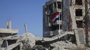 Le drapeau syrien flotte au milieu de bâtiments en ruines à Deraa al-Balad, le 12 juillet 2018.