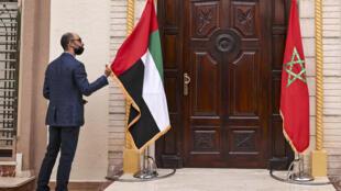 رجل يعدل علم الإمارات في القنصلية الجديدة لدولة الإمارات العربية المتحدة في العيون، المدينة الرئيسية في الصحراء الغربية المتنازع عليها في 4 تشرين الثاني/نوفمبر، 2020