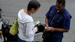 A couple holding new Bolivar-notes talks in downtown Caracas on August 21, 2018