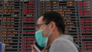 Un hombre con mascarilla protectora habla por teléfono ante un panel informativo repleto de vuelos cancelados en el aeropuerto internacional de Shanghái Pudong, el 26 de marzo de 2020 en la ciudad china