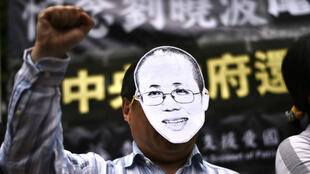 Un manifestant porte un masque représentant Liu Xia, lors d'un hommage à Liu Xiaobo, en août 2017, à Hong Kong.