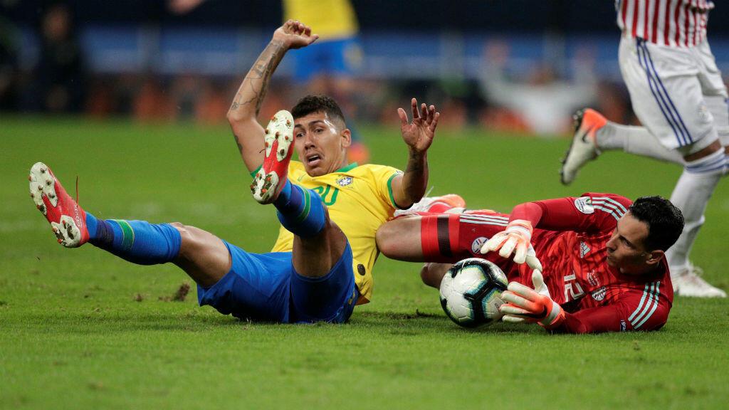 El delantero brasileño Firmino cae en el área después de un choque con el defensa paraguayo Fernando Balbuena. Porto Alegre, Brasil, 27 de junio de 2019.
