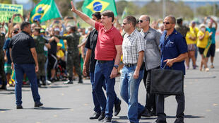 Brazil's President Jair Bolsonaro gestures after joining his supporters, who were taking part in a motorcade to protest against quarantine and social distancing measures, amid the coronavirus disease (COVID-19) outbreak, in Brasilia, Brazil April 19, 2020.