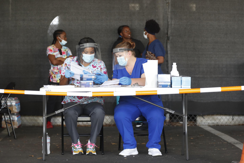 """Des personnels soignants se préparent à tester des patients dans un """"drive-in"""" mis en place à cet effet à St. Petersburg, en Floride, le 8 juillet 2020."""