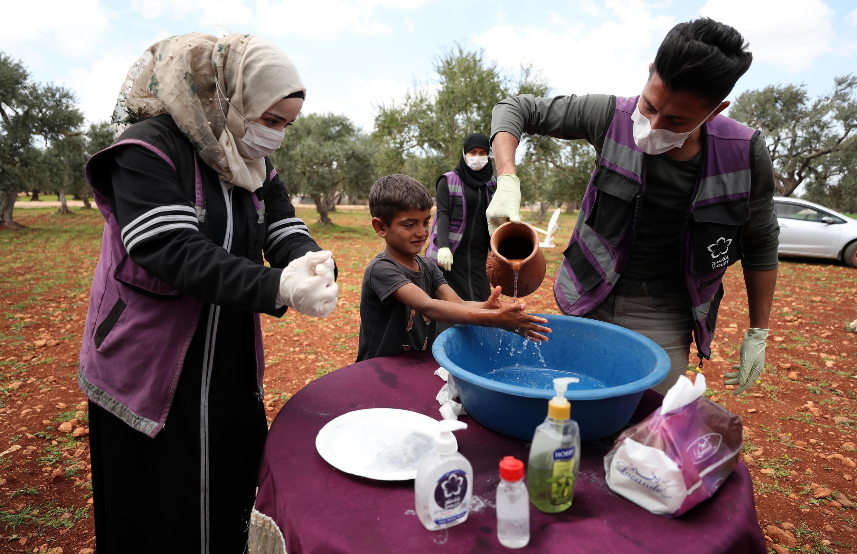 Voluntarios enseñan a un niño cómo lavarse las manos adecuadamente en un campamento para sirios desplazados en una aldea al norte de Idlib, Siria.