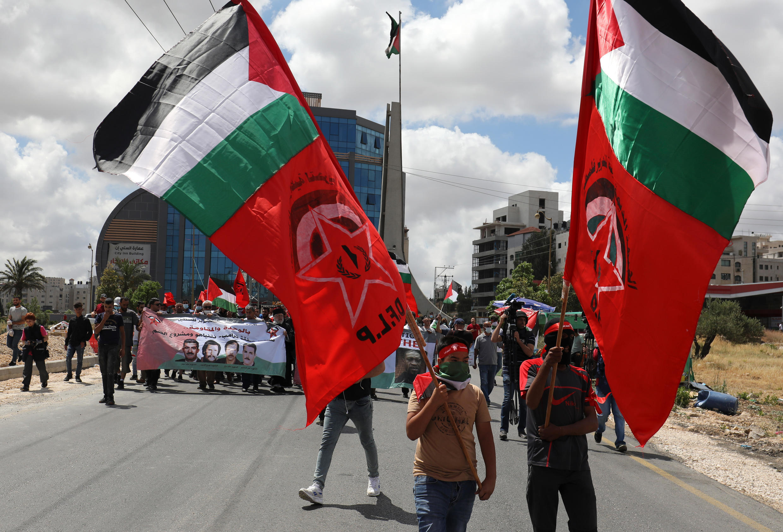 صورة أرشيفية لمتظاهرين فلسطينيين يحملون الأعلام في 19 حزيران/يونيو، خلال تظاهرة بالقرب من مدينة رام الله في الضفة الغربية المحتلة رفضا للمخطط الإسرائيلي للضم