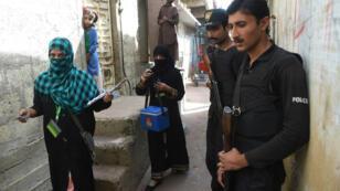 Un policier escortant un vaccinateur à Karachi, le 12 janvier 2016.
