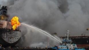 رجال إطفاء على متن سفينة يحاولون إطفاء حريق على متن ناقلة النفط الاندونيسية في بيلاوان في سومطرة الشمالية في 11 ايار/مايو 2020.
