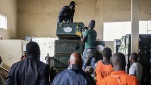 Des membres de la commission électorale mozambicaine déchargeant des urnes à Maputo, la capitale.