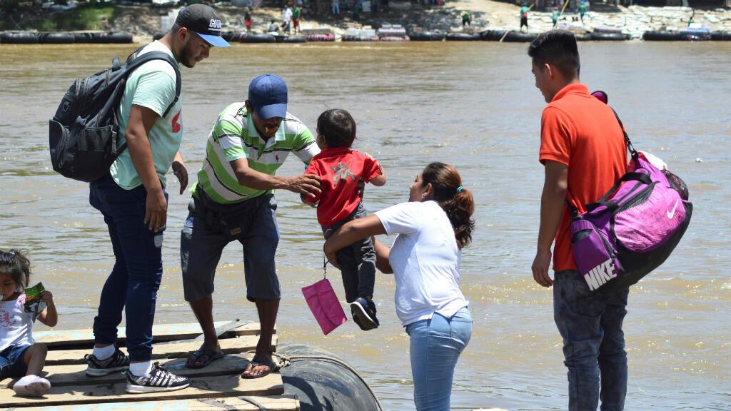 Un hombre ayuda a un migrante guatemalteco a abordar con su hijo en una balsa para cruzar a Ciudad Hidalgo, México, como se ve desde Tecun Uman, Guatemala, el 17 de julio de 2019.