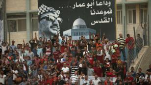 Des supporters palestiniens sous le portrait de Yasser Arafat, lors d'un match disputé en Cisjordanie.