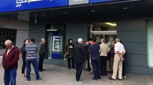 Des Libanais font la queue à l'extérieur d'une agence Fransabank, le 1er novembre 2019, à Tripoli au Liban.