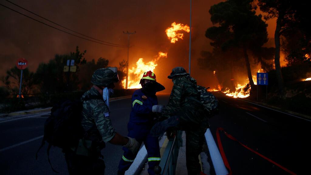 Los bomberos y los soldados retroceden cuando un incendio forestal continúa tomando terreno en la ciudad de Rafina, cerca de Atenas, Grecia, el 23 de julio de 2018.