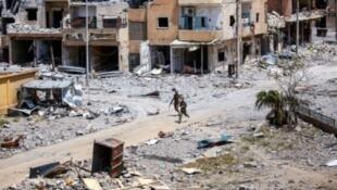 مقاتلان من قوات سوريا الديمقراطية وسط مبان مدمرة في الرقة في 28 تموز/يوليو 2017